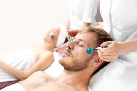 Photo pour Massage facial pour deux. Une femme et un homme sur un traitement de soins dans un salon spa. - image libre de droit