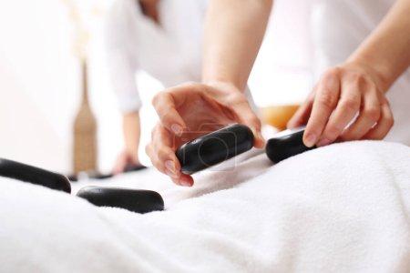 Photo pour Spa pour deux. Massage avec pierres pour elle et lui. Une femme et un homme sur un massage dans un salon spa. - image libre de droit
