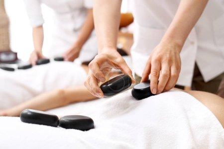 Photo pour Pour les amateurs de massage avec des pierres. Une date au spa, massage avec pierres pour elle et lui. - image libre de droit
