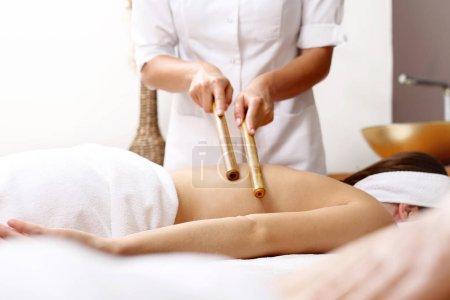 Photo pour Massage au bambou. Le masseur masse le corps à l'aide de bâtons de bambou . - image libre de droit
