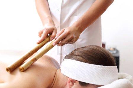 Photo pour Massez avec des baguettes de bambou. Le masseur masse le corps à l'aide de bâtons de bambou . - image libre de droit