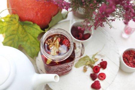 Sala de té, té de frambuesa de otoño. Té de hierbas de flores de tilo con frambuesas .