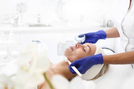 Photo pour Masque facial. La femme dans le salon de beauté, esthéticienne, appliqué avec un pinceau sur le masque du visage. - image libre de droit