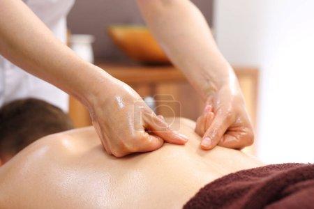 Photo pour Massage du dos. Le masseur masse son dos . - image libre de droit