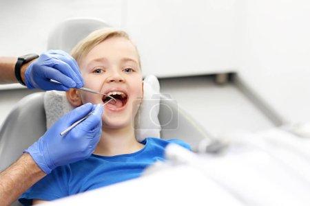 Photo pour Aperçu de l'hygiène buccodentaire. Un enfant dans une chaise dentaire pendant un traitement dentaire - image libre de droit