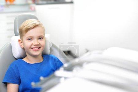Photo pour La dentisterie, un enfant joyeux dans une chaise dentaire - image libre de droit