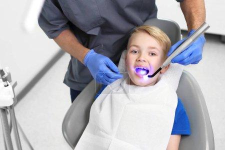 Photo pour Phoque phoque photopolymérisateur, un enfant dans un cabinet dentaire - image libre de droit