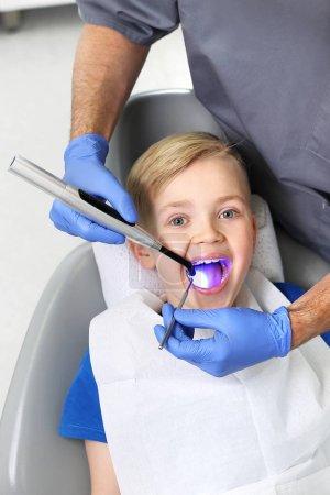 Photo pour Enfant chez le dentiste. Phoque phoque photopolymérisateur, un enfant dans un cabinet dentaire - image libre de droit