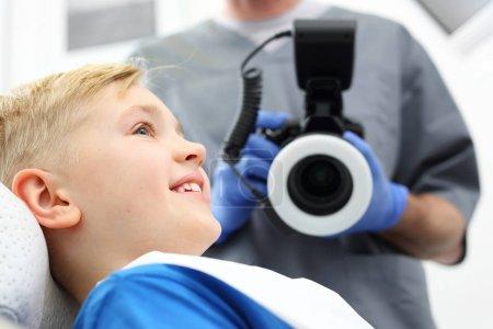 Photo pour Enfant chez le dentiste. Un enfant dans une chaise dentaire pendant un traitement dentaire - image libre de droit