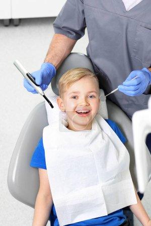 Photo pour Aperçu de l'hygiène buccodentaire. La dentisterie, un enfant joyeux dans une chaise dentaire - image libre de droit