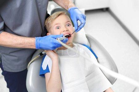 Photo pour Peur du dentiste. Enfant effrayé dans une chaise dentaire . - image libre de droit