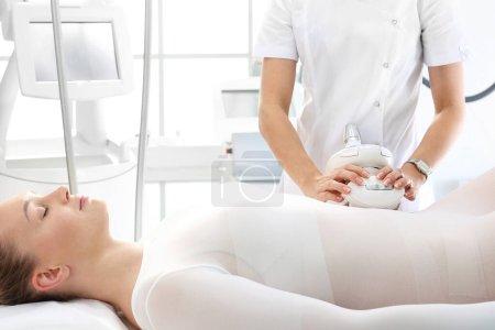 Photo pour Femme dans une clinique de cosmétiques recevant des soins corporels. - image libre de droit