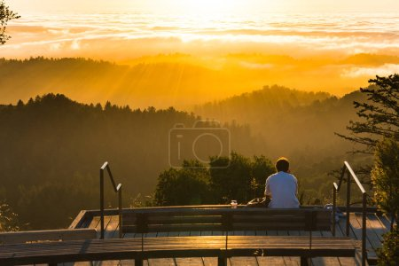 Photo for Solitary figure watches sunset over hazy forested hills - Royalty Free Image