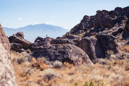 Woman stands on top of a large stone in the Happy Boulder rock climbing area near Bishop, California