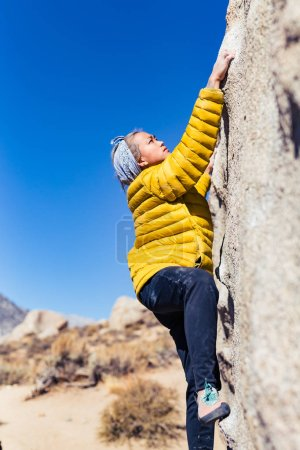 Petite asian woman rock climbing outdoors hangs from stone wall while wearing a bright yellow puffy jacket