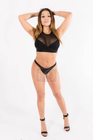 Young fit hispanic woman in black two piece and black high heels posing on a white background