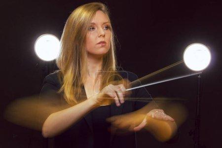 Photo pour Jeune femme caucasienne chef d'orchestre gestes avec bâton et laisse des pistes de lumière - image libre de droit