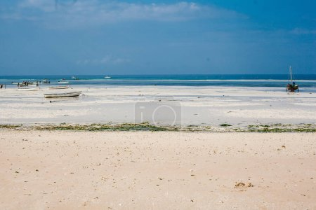 African beach with white sand on the indian blue ocean and blue sky