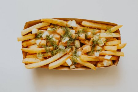 Photo for Top view of tasty french fries with dill in box on grey - Royalty Free Image