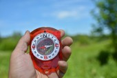 Compass in hand. Magnetic compass is in the hand of the person on a background summer landscape.