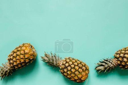 Ripe pineapples border frame on turquoise backgrou...