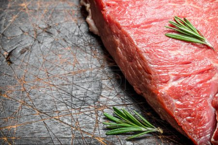 Photo for Raw meat. A piece of beef with rosemary. On a wooden background. - Royalty Free Image