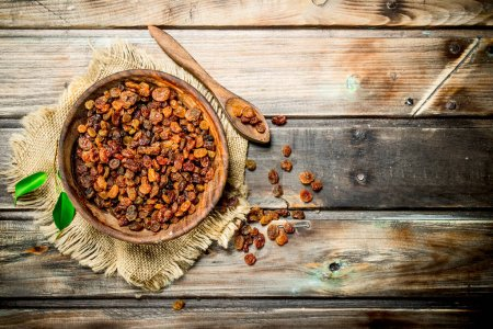 Photo for Raisins in bowl. On a Wooden background. - Royalty Free Image