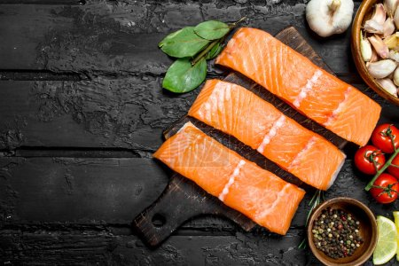 Photo for Raw salmon fish filet with spices and herbs. On black rustic background. - Royalty Free Image