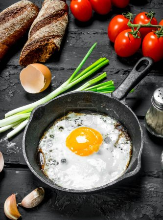 Photo for Fried egg in a pan with bread and tomatoes. On black rustic background. - Royalty Free Image