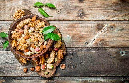 Photo for Different kinds of nuts in bowl with leaves. On a wooden background. - Royalty Free Image