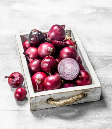 Photo for Red onion whole and sliced on tray. On rustic background - Royalty Free Image