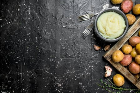 Photo for Mashed potatoes in a bowl with garlic and thyme. On black rustic background. - Royalty Free Image