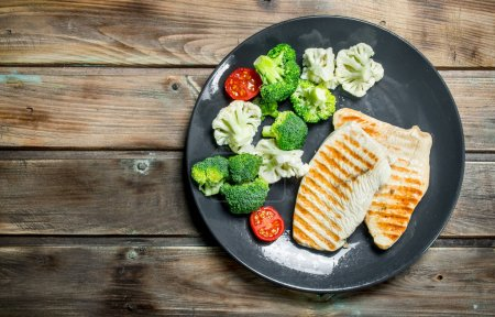 Photo for Fried chicken steak with broccoli in a plate. On a wooden background. - Royalty Free Image