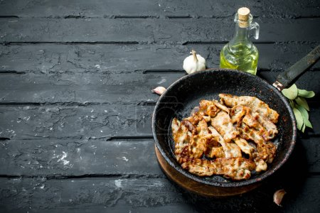 Photo for Fried bacon with spices. On black rustic background. - Royalty Free Image