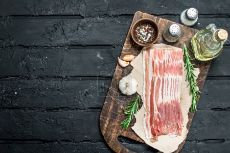 Photo for Raw bacon with rosemary and spices. On black rustic background. - Royalty Free Image