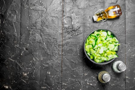 Photo for Vegetable salad. Simple salad of cucumbers and Chinese cabbage with olive oil and spices. On black rustic background. - Royalty Free Image