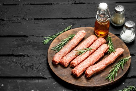 Photo for Raw sausages from beef with rosemary. On black rustic background. - Royalty Free Image