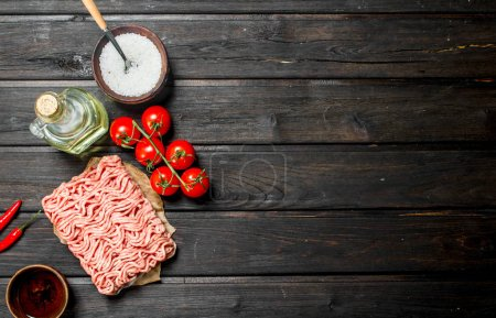 Photo for Raw ground beef with tomatoes and spices. On a wooden background. - Royalty Free Image