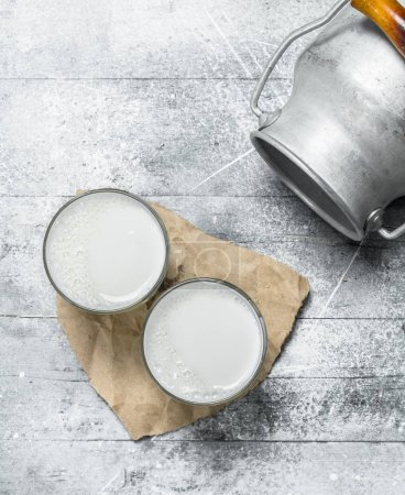Photo for Milk in glasses with a can. On a rustic background . - Royalty Free Image