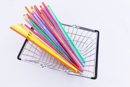 Brightly coloured drinking straws in a miniatute shopping basket
