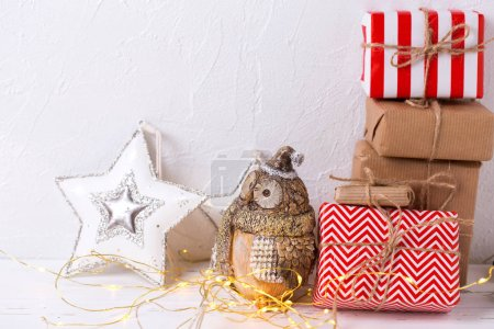Colorful wrapped gift boxes with presents, decorative owl and  star on white textured background. Selective focus.Place for text.