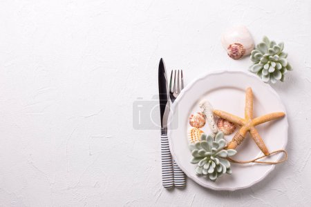 Summer table setting. White plate, shells, cutlery, coral, sea sta, succulent echeveria on white textured  background. View from above. Selective focus. Place for text.