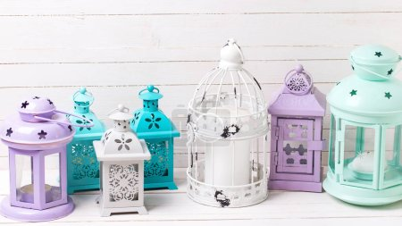 Bright decorative lanterns on white wooden background. Shabby chic decorations. Selective focus.