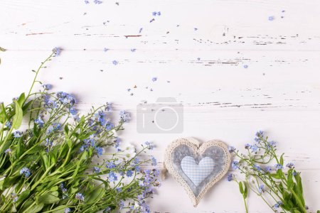 Frame from blue forget-me-nots or myosotis flowers and heart on white wooden background