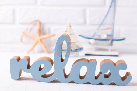 Word relax and marine decorations on grey textured background