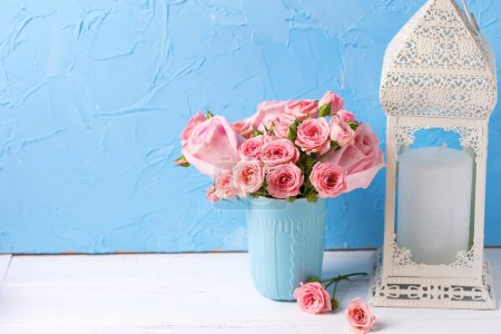 Pink roses flowers in blue cup against blue textured wall