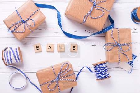 Word sale made from wooden blocks and gift boxes with presents, blue ribbons on textured wooden background