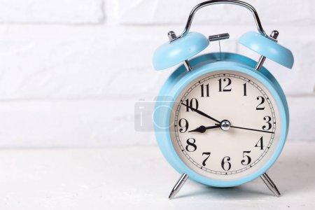 Photo pour Réveil bleu sur fond blanchi près d'un mur de briques. Concept du temps. Concentration sélective. Place pour le texte . - image libre de droit