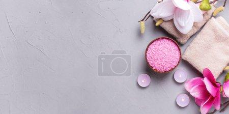 Photo pour Serviettes, sel de mer dans un bol, bougies allumées et fleurs de magnolia rose sur fond gris texturé. Concept de spa. Concentration sélective. Endroit pour le texte. Pose plate. Forme longue bannière . - image libre de droit