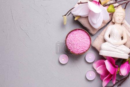 Photo pour Sel marin, bougies allumées, fleurs de Bouddha et de magnolia rose sur fond gris texturé. Concept de spa. Concentration sélective. Endroit pour le texte. Pose plate . - image libre de droit